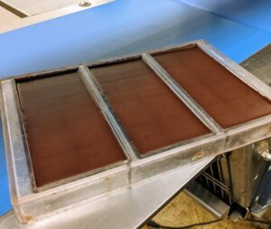 Once made, the chocolate is poured into bar shaped moulds, cooled, set, and chilled.