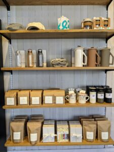 The shelves also contain charming accessories such as hats, mugs, travel tea cups, and other items.