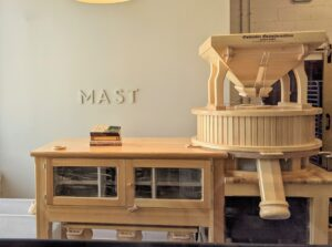 Mast is located in the heart of Mount Kisco in a 10-thousand square foot facility. The light and airy interior houses a sit-down cafe, a large retail space, an open kitchen, and its own packaging and shipping center. This is a flour mill where the grains are stone-milled into flour and sold in the Mast Market.