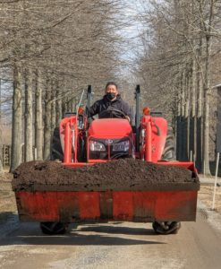 Here comes Phurba on our trusted Kubota model M7060HD12 tractor – a vehicle that gets lots of use at the farm for pulling or pushing agricultural machinery or trailers, for plowing, transporting mulch and compost, and so much more.