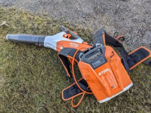 He is using a STIHL backpack battery. This battery eliminates the cost of fuel and engine oil and can be used with this handheld blower. The backpack battery can be plugged in to power the blower, which is less noisy and perfect for around my Winter House and in the beds. The back battery design shifts the weight from the unit to the back or the hip for easier carrying and less fatigue. Plus, the blower can be used both from the right side and the left side depending on the user.