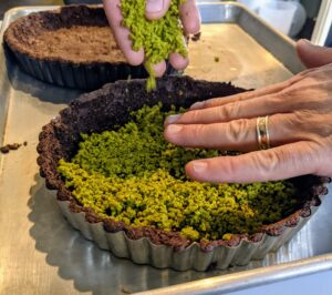 """Once the crusts are done, they are covered with chopped pistachios. You'll find pistachios everywhere in this dessert. They are embedded in the crust, in a paste layered beneath the milk-chocolate filling, and in a dusted coating on top. I first made this recipe in Episode 501 of my television show, """"Martha Bakes."""""""