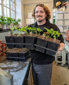 In the head house, Ryan continues to transplant flower and vegetable seedlings. We grow so many plants from seed. We start in January and continue until it's time time to plant directly into the outdoor garden beds.
