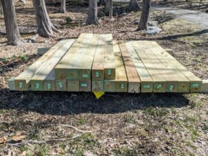 A stack of 5 x 5 posts are delivered to the pumpkin patch site. These posts will secure the new fence planned for the garden.