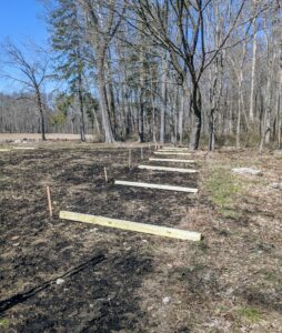 Each pine post is eight feet long. It will be buried three feet leaving a five foot fence all the way around the space.