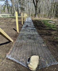 This roll of fencing fabric is from a company called Red Brand Fence Co. in Peoria, Illinois – the only company in the world that makes this type of fencing. Pete and Fernando unroll the fence fabric along the side of the posts and attach it from the top to the bottom.