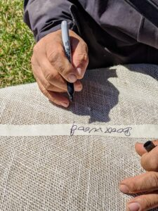 Once the burlap is rolled and tied, Phurba labels the roll indicating what it covers and where. The label will make it easy to identify next fall when the boxwood is covered again.