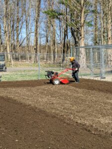 Phurba starts tilling the beds on one side of the garden and goes counter-clockwise around and around the entire space.