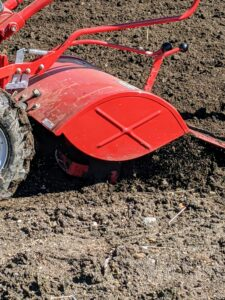 The machine is set to till the soil at about six to eight inches deep. On some tillers, the speed of the rotating tines helps determine the speed of the machine.