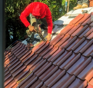 One by one, each clay tile is affixed to the roof through the various protective membranes. This roof has a 75-year warranty - the longest for any residential roof.