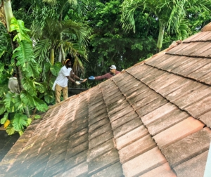 The tiles are then handed down one at a time to crew members working on the roof...