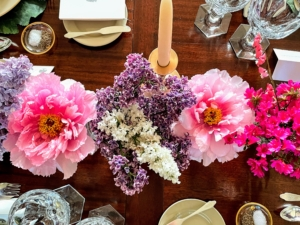 Here - lighter pink peonies with lilacs in the center. And any glass will do for a bud vase. The table looks so cheerful and inviting.