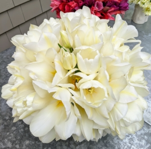 Here's an all white arrangement - so filled with gorgeous pure white tulips, one cannot even see the vessel in which they are displayed.