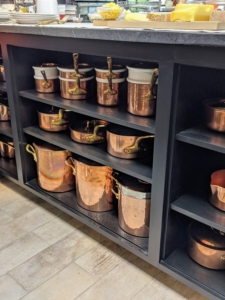 All the exposed shelves are now black and filled with gorgeous copper pots.