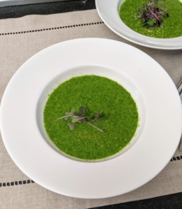 The soup is served garnished with a few micro greens.