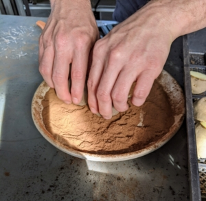 Next, Ryan takes each cut side of a potato and coats it with Douglas fir bark dust.