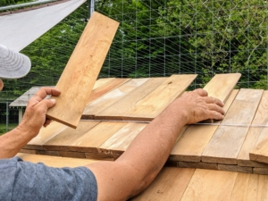 This part of the process takes longer since all the shingles are nailed individually, each overlapping the one above it. Fernando works from the opposite end positioning the shingles in another row, so Pete can nail them.