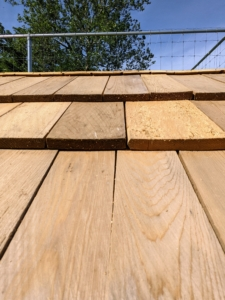 Here's a closer view of the attached shingles. Each one is rectangle and about 16 inches long. Wood shingles are thin, tapered pieces of wood primarily used to cover roofs to protect them from the weather.