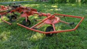 It uses a rotary motion to grab the hay with spinning tines and then cast it out the back of the machine.