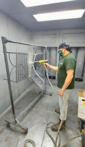 """The primer is left to dry and then it's time to powder coat. Powder coating is applied as dry powder through an electrostatic process, then cured with heat. It can be used on different surfaces, including metal, concrete and steel, Here, one can see the dark primed areas getting powder coated with color - """"Bedford Gray."""" Below is a short video of how evenly and carefully the powder coating is applied. This step also takes about 15-minutes per coat."""