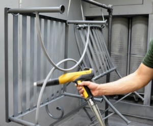 Next, the furniture is brought into a special spraying booth where the pieces are coated with zinc-rich primer. The zinc-rich coating provides corrosion resistance and adds to the durability of the furniture. The primer is delivered through a vibrating machine and hose and then carried through the nozzle with electrostatic charge. This process takes about 15-minutes per piece.