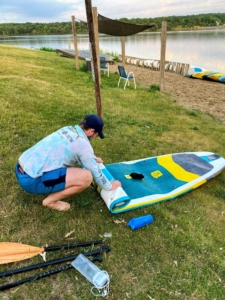 And it is so easy to store because it can roll up to the size of a sleeping bag. Here's Garrett rolling the board as it deflates. Inflating it back up is also very easy. The high-quality dual-action pump with gauge inflates it in less than 10-minutes.