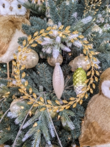 This non-traditional wreath is perfect for both classic and more contemporary holiday settings. It is designed with a pattern of rhinestone leaves on a metal form. It measures approximately 12 inches in diameter.