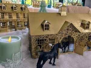 And for this season, we made artful metallic houses modeled after the outbuildings at my Bedford, New York farm. The one in front is my stable. In the back is a miniature version of my Winter House. I also offer a model of my Summer House. Lights shine through all the windows of these gold-toned structures. They're great on a table or along a wide windowsill where guests can see them.