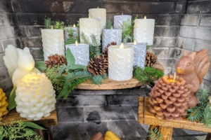 """In the fireplace is a nice assortment of flameless candles - my Cable Knit Pillar candles available in ivory, Bedford gray and red, and my Figural Squirrel candles. """"Lighting"""" them with the remote is so easy and quick."""