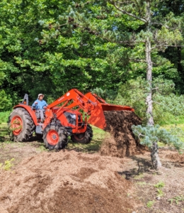 Because the pinetum covers a good portion of this area, it takes a couple of days to complete this task, but the results are so worth the effort. Here is Chhiring using our Kubota model M7060HD12 tractor to transport another large load of mulch to the back of the pinetum. This tractor is used every single day for our outdoor chores.