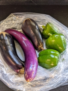 We also harvested a few eggplants. I like to pick them when they're smaller - when they are young and tender. Picking a little early will encourage the plant to grow more, and will help to extend the growing season. Sweet peppers are often harvested when the fruit is still green, but full sized. We picked three bell peppers, but more are growing in the garden bed.