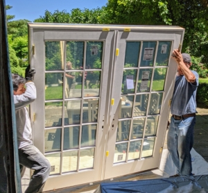 The doors are carefully carried to the opening and fitted perfectly level and plumb. These Pella hinged French doors allow true light into the room while maintaining exceptional energy efficiency.