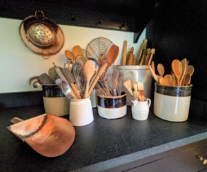 Everything was washed and returned. Crocks and other antique or vintage ceramic containers house wooden spoons and other cooking utensils for easy access.