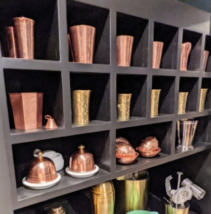 More copper and brass decorate the cubbies at the other end of this large built in shelving unit.
