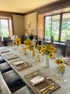 Along this dining room table, small vases of rudbeckia with their bright, showy flower heads. Rudbeckia flower colors include yellow and gold, and the plants grow two to six feet tall, depending on the variety.