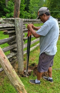 To remove one, Pete digs around the post by hand using a post hole digger, a hand tool used to manually dig deep and narrow holes in order to install fence posts.