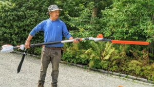 Chhiring is holding a STIHL telescoping hedge trimmer which features precision-ground cutting blades and anti-vibration technology so are hands steady during every job. At the end of every STIHL blade tool is the bright orange protective scabbard.