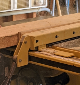 Then, the cut piece of lumber is passed through the table saw.