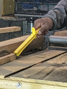 This bright yellow push stick allows one to safely feed material through the table saw. The push stick has a comfortable pistol grip handle with an anti-slip guard and a notched end to help maintain even pressure as the wood is moved.