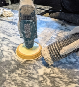 Next, Benicio uses a very fine grit sandpaper over the seams to make sure any remaining epoxy is removed and the two surfaces are even and smooth. A vacuum is used alongside the sander to remove any dust.