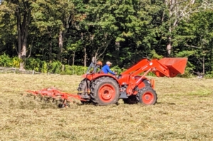 Here is Domi driving the tedder up and down the field as the machine takes all the greener hay from the bottom and turns it over to dry.