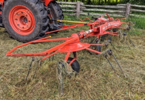 The tedder uses a rotary motion to grab the hay with spinning tines and then cast it out the back of the machine.