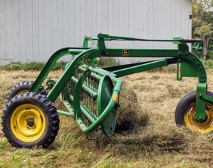 A side view shows the hay being gathered together by the rake's tines.
