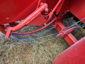 These are the twine strands that unravel and wrap as the bales move through the baling machine. A measuring device—normally a spiked wheel that is turned by the emerging bales—measures the amount of material that is being compressed and then knotters wrap the twine around the bale and tie it off.