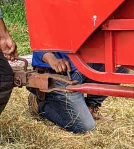 The baler and tractor are connected by a simple trailer hitch pin and clip.