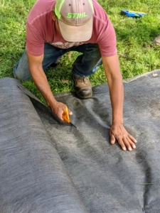 Pete cuts the weed cloth to size, making sure all the edges are perfectly straight.