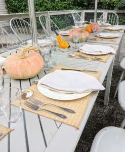 The table was set with pumpkins and light colored plates and napkins.
