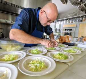 Chef Pierre begins to construct the salads. First, a bed of frisee. Frisée, also known as curly endive in the UK, is a frizzy salad green of the chicory family along with endive, escarole, and radicchio. Frisee is a tousled head of lacy ruffles, sprouting from a pale yellow core.
